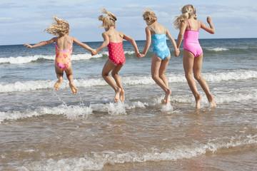 Girls in bathing suits splashing in ocean