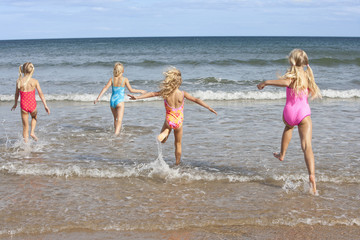 Girls in bathing suits running in ocean