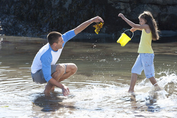 Father and daughter playing in tide pool
