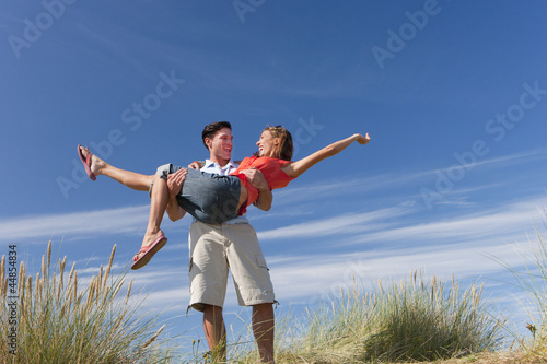 Man carrying woman on sunny beach
