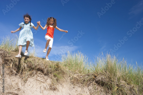 Girls holding hands and jumping on sunny beach