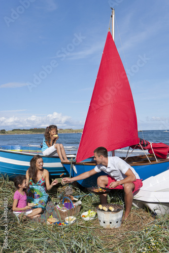 Family with barbecue picnicking near boats on beach