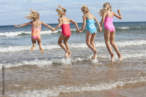 Girls in bathing suits splashing in ocean