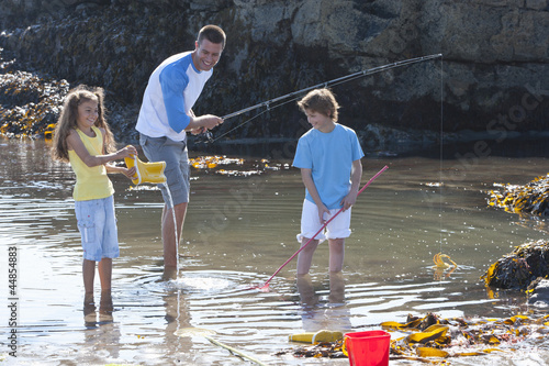 Father fishing with daughter and son in tide pool