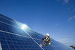 Engineer with digital tablet inspecting solar panels