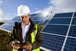 Engineer with digital tablet standing in front of solar panels