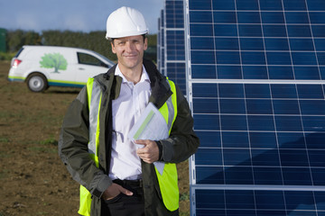 Portrait of smiling engineer standing next to solar panels
