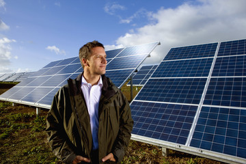 Farmer standing in front of solar panels