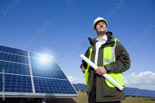 Engineer with blueprint in front of solar panel