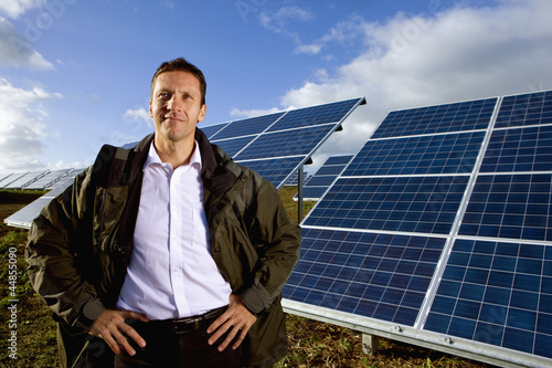 Portrait of smiling farmer standing in front of solar panels