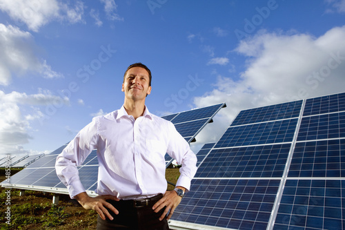 Portrait of smiling man standing in front of solar panels