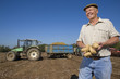 Smiling farmer holding potatoes in sunny, rural field with tractor and trailer in background