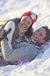 Portrait of smiling couple laying in snow