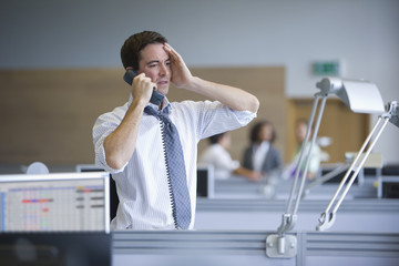 Businessman talking on telephone with head in hands in office