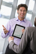 Businessman showing businesswoman graph on digital tablet