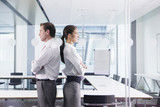 Businessman and businesswoman standing back to back in conference room