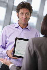 Businessman showing businesswoman graph on digital tablet