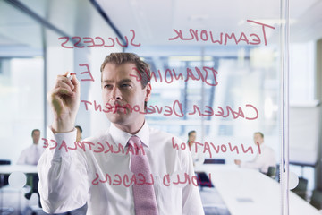 Businessman writing on glass window in office