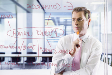 Businessman looking at flow chart on glass window