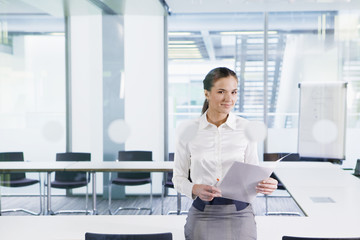 Portrait of smiling businesswoman holding paperwork in conference room