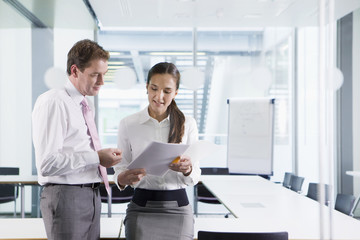 Businessman and businesswoman discussing paperwork in conference room
