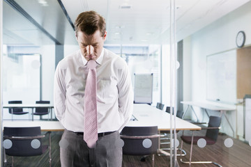 Dejected businessman leaning on glass window in conference room