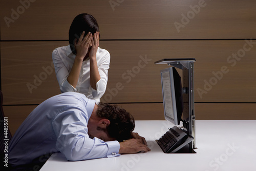 Exhausted businessman and businesswoman at desk in office