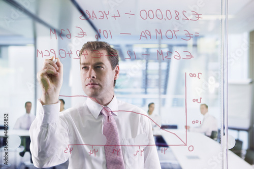 Businessman drawing graph on glass window in office