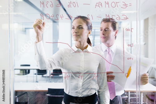 Businessman and businesswoman drawing chart on glass window in office
