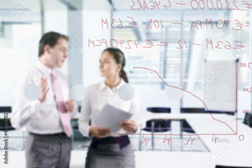 Businessman and businesswoman talking in conference room with graph on glass window in foreground