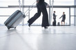 Rushing businesswoman pulling suitcase in airport