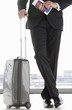 Businessman holding passport and leaning on suitcase