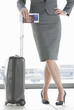 Businesswoman holding passport and leaning on suitcase with hands on hips