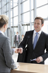 Businessman handing passport to woman at airport counter