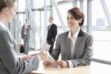 Woman checking businesswomanճ passport at airport counter