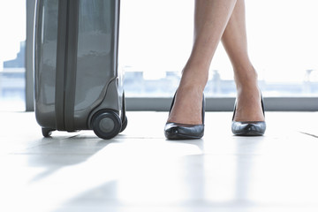 Close up of suitcase and businesswomanճ high heels