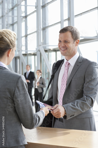 Smiling businessman handing passport to woman at airport counter