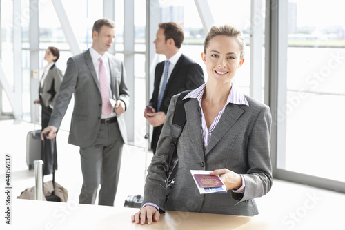 Portrait of smiling businesswoman holding passport at airport counter