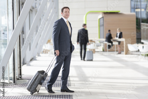 Businessman with suitcase arriving at airport
