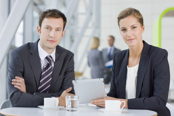 Portrait of confident businessman and businesswoman using digital tablet