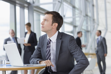 Pensive businessman in suit sitting at laptop in lobby