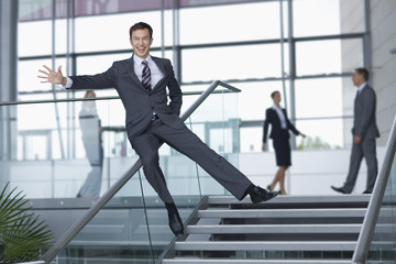 Portrait of enthusiastic businessman in suit sliding down railing in lobby