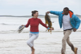 Young man with seaweed chasing girlfriend on beach