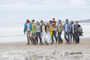Large group of friends walking on beach
