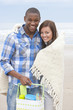 Portrait of smiling young couple with blanket and basket on beach