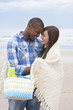 Young couple with blanket and basket hugging face to face on beach