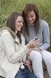 Smiling young women looking at text message on cell phone in grass