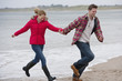 Playful young couple holding hands and running on beach