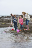 Family fishing on rocks with nets