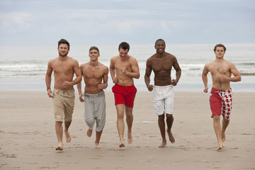 Smiling young men running bare chested on beach